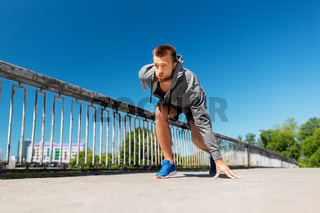 young man running across city bridge