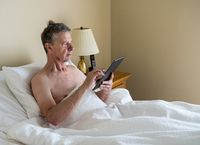 Single caucasian senior man in inclined bed and reading from digital tablet