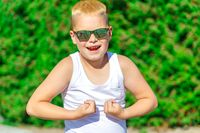 handsome blond boy in sunglasses shows muscles in nature in summer