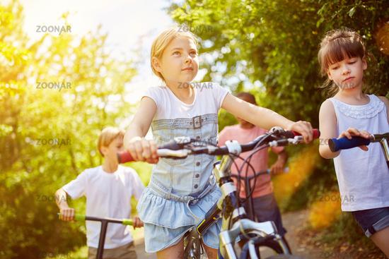 Kinder fahren mit Fahrrad und Roller im Sommer
