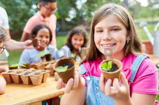 Mädchen mit Setzlingen lernt über Pflanzen