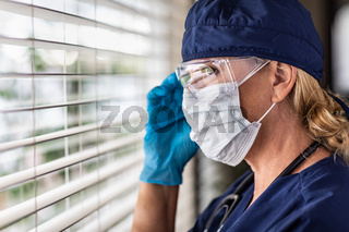 Female Doctor or Nurse On Break At Window Wearing Medical Face Mask and Goggles