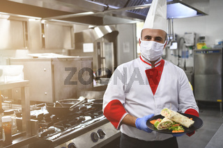 chef cook wearing face protective medical mask for protection from coronavirus