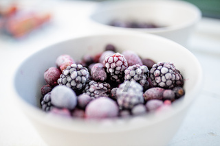 Bowl of dark berries on a white table