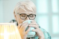 Senior Woman Wrapped In A Checkered Plaid Is Drinking Tea At Home