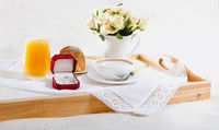 Wooden tray with breakfast and engagement ring