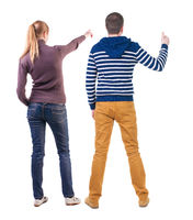 Back view of couple in sweater pointing.