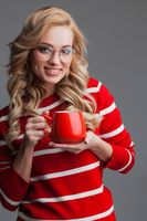 Beautiful woman in glasses holding red cup