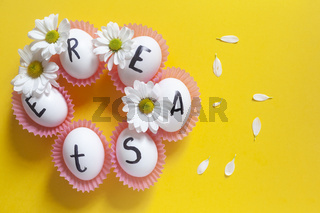 Happy Easter. Easter text on white eggs with spring flowers