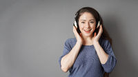 happy smiling young woman listening to music with headphones