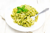Pasta with pesto sauce in plate on wooden board