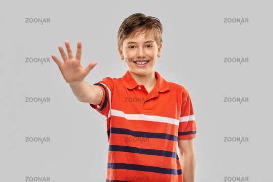 portrait of happy smiling boy showing five fingers