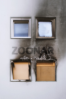house or home fire - burned out apartment with boarded up windows and building facade blackened by soot