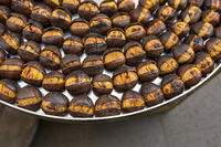 Roasted chestnuts nicely laid out on an iron tray