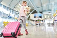 Alleinreisendes Kind mit Koffer im Flughafen Terminal