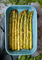 Roasted asparagus seasoned with salt, pepper, garlic and decorated with fresh herbs