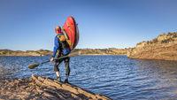 kayak portaging on lake shore
