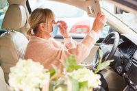 Frau mit Mundschutz in Fahrzeug überprüft ihre Maske