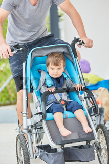 Vater transportiert Kind im Kinderwagen Fahrrad
