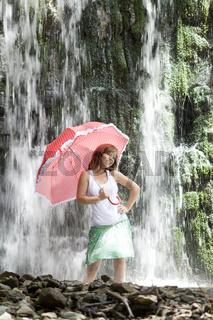 Junge Frau mit Schirm im Wasserfall