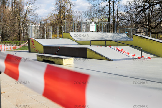 Corona virus COVID-19 restriction. No people due to quarantine. Closed urban skate park. Empty park and playground. Stay at home compaign. Red warning tape on ramps and slides. Social distancing
