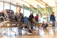 Casual blond young woman using her cell phone while waiting to board a plane at bussy airport departure gates.