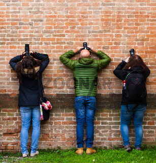 three photographers shooting upwards leaning against the wall