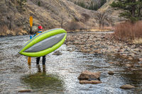 paddler carrying  inflatable whitewater kayak