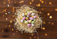easter eggs in straw nest on wooden table