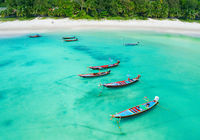 Aerial view of longtail boats and tropical sea