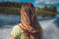 a young woman with long hair rides a fast boat on the water surface of the lake. Back view. Against the background of a white foam trail from the propeller and green shores receding into the distance