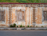 Aged house with weathered ornamental wall and shuttered windows under green hill by asphalt road