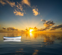 White rowing boat adrift on open ocean and drifting towards the sunset