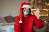 Caucasian guy in face mask and Santa Claus hat looking at camera