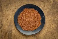 red quinoa grain on ablack plate