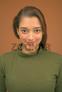 Young beautiful Indian woman against brown background