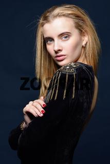 beautiful blonde woman in black velvet dress with epulet.