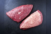 Raw dry aged wagyu cap of rump beef offered as top view on black background with copy space