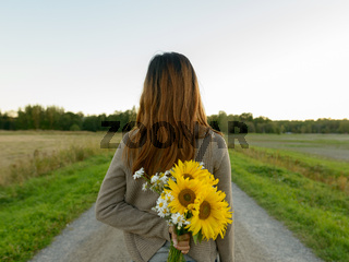 Rear view of young Asian woman holding sunflowers behind back in nature