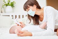 Mutter und Baby beim Fieber messen mit Thermometer
