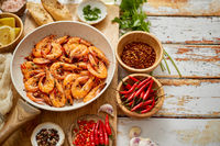 Top view of prawns shrimps roasted on pan with herbs placed on rustic wooden kitchen table