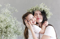 Young brunette mother and little daughter stand near the wall with big flowers wreath