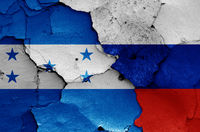 flags of Honduras and Russia painted on cracked wall