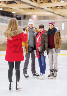 happy friends taking photo on skating rink