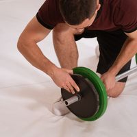 Adding weight to a barbell young man bow on a knee changing black and green plates, equipment for weight training concept. Sports equipment for training. square cropped