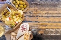 Tapas, pinchos, and wine, shot from above on a wooden table. Cheese, jamon and olives, spicy gildas and potato chips in a street cafe with copy space