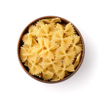 Top view of uncooked farfalle pasta in clay bowl