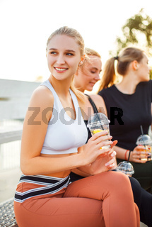 Young sportswoman with fresh drink sitting near friends