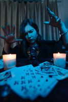 Woman fortune-teller guesses fate of night at table with candles