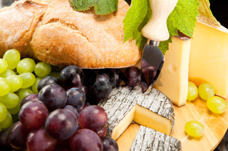 Cheese plate with red and green wine grapes